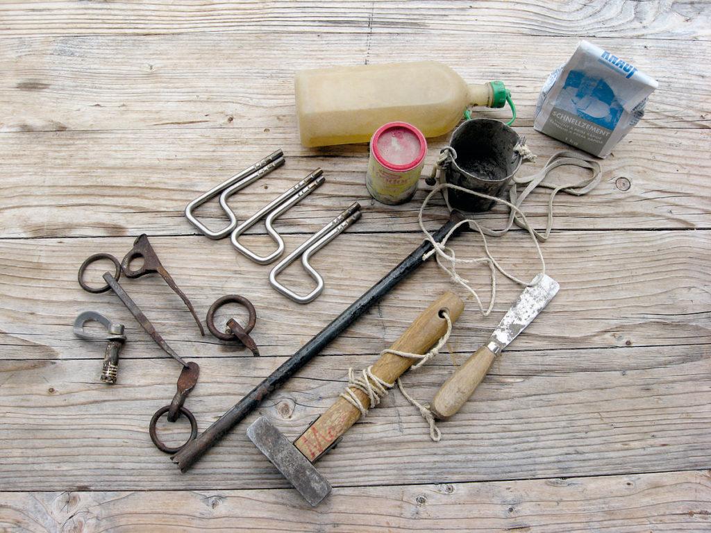 Das Bild zeigt das von Ossi Bühler verwendete Werkzeug zum Setzen von Bühlerhaken (Hammer, Bohrmeisel, Spachtel, Wasserflasche, Zement, Zementschale und Bühlerhaken).