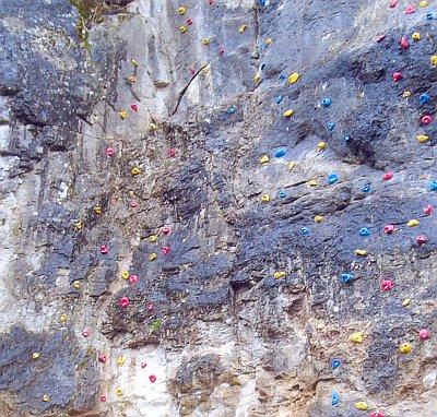 Das Bild zeigt eine Felswand mit künstlichen Klettergriffen aus Plastik