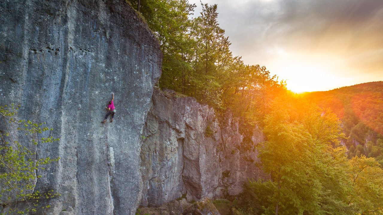 Das Bild zegt einen Kletterer während des Sonnenuntergangs in der Kletterroute Sautanz an den Oberen Gößweinsteiner Wänden