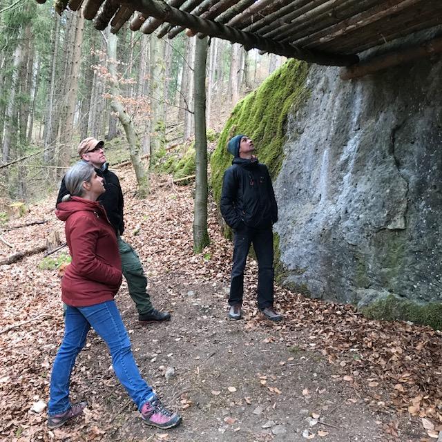Das Bild zeigt drei Personen, du unter einem zum Bouldern illegal errichteten Podest stehen