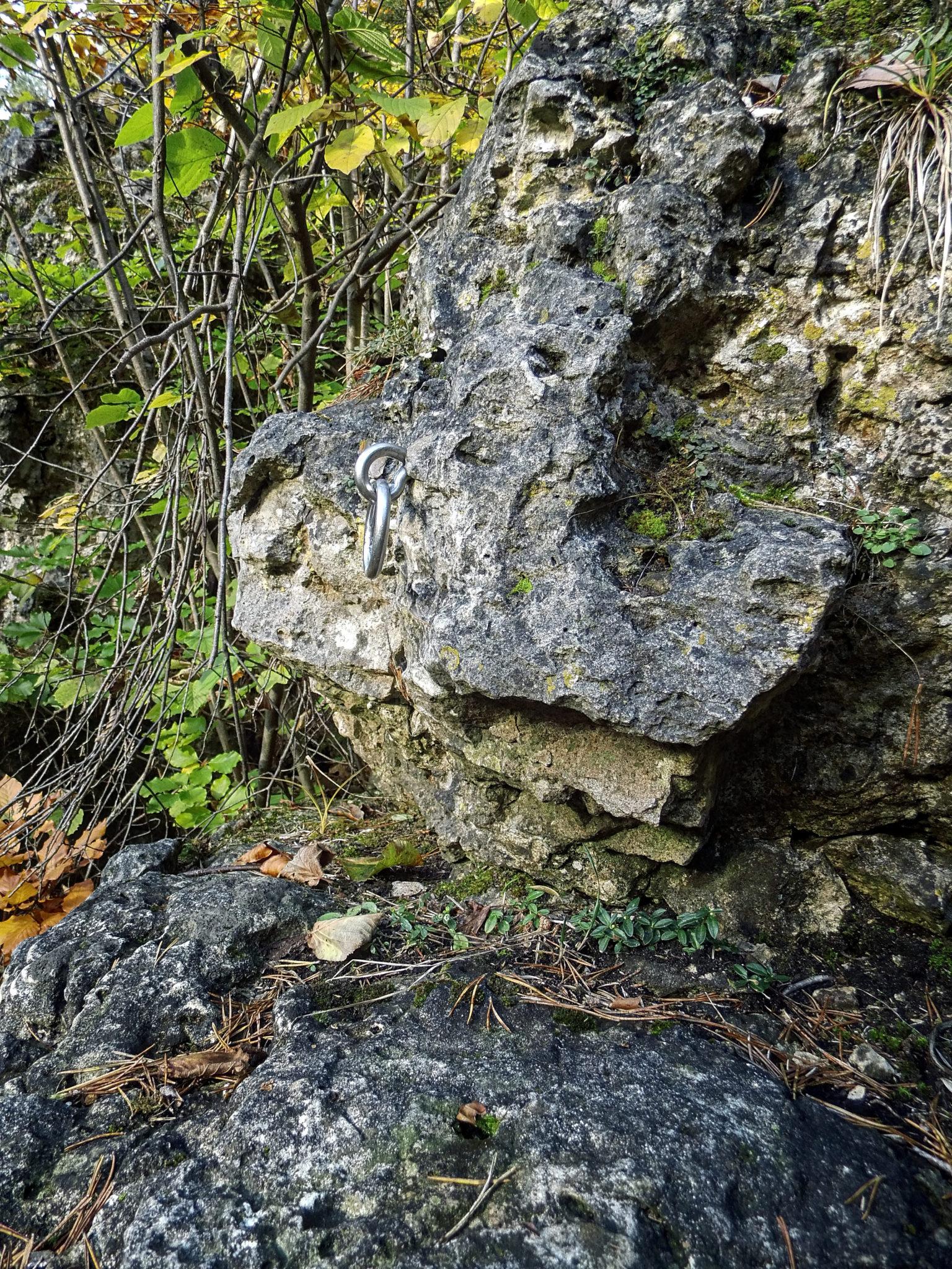 """Das Bild zeigt einen Umlenkhaken in """"morschem"""" Gestein vor einem Auzugsversch"""